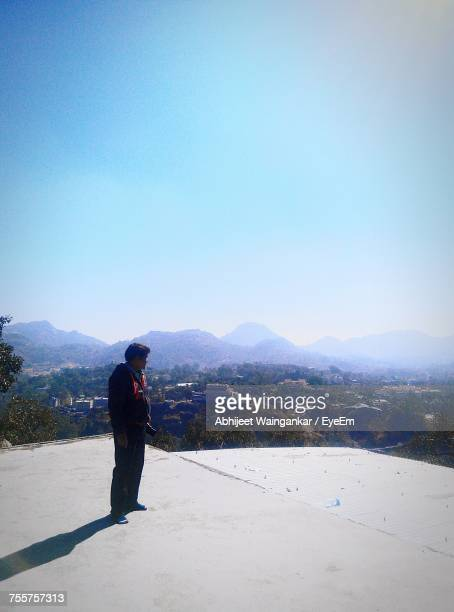 Man Standing On Rooftop Against Sky On Sunny Day