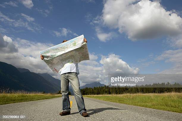 Man standing on rural road holding road map, head obscured by map