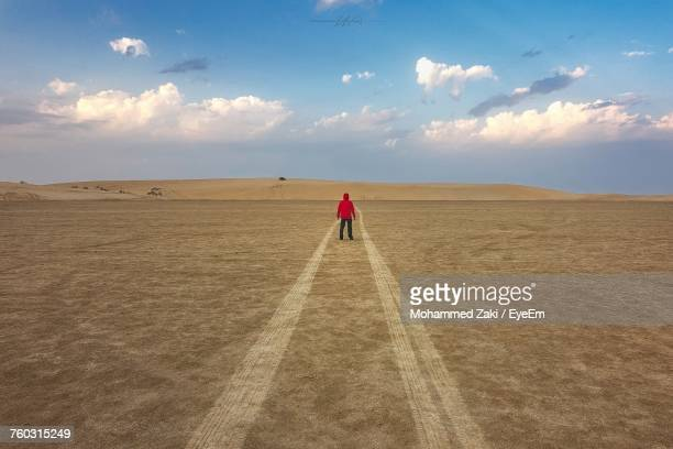 Man Standing On Sand Against Sky