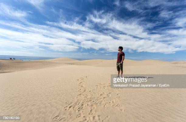 Man Standing On Sand At Beach