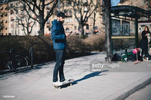 Man standing on skateboard while using mobile phone by bus stop in city
