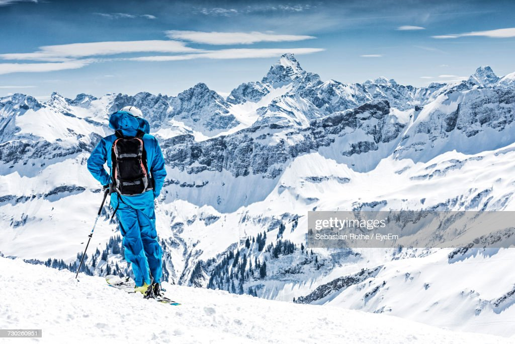 Man Standing On Snow Covered Landscape Against Sky : Stock Photo