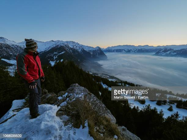man standing on snow covered mountain against sky - principality of liechtenstein stock pictures, royalty-free photos & images