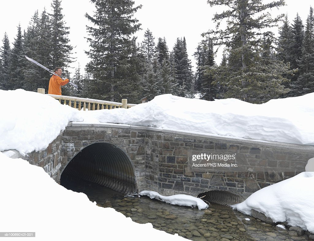 Man standing on snow covering bridge holding skis, looking away, side view : Stockfoto