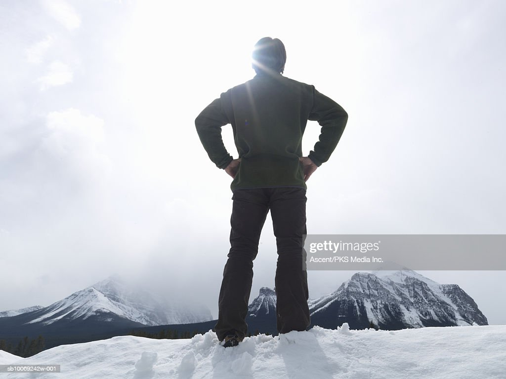 Man standing on snow covering mountain top, rear view : Stockfoto