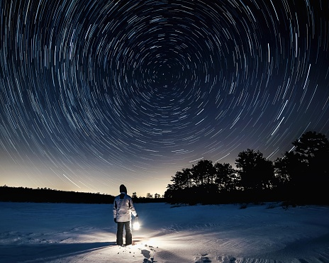 Man Standing On Snow Field Against Sky At Night - gettyimageskorea