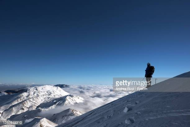 man standing on snowcapped cervino mountain against clear sky - andrea rizzi stock pictures, royalty-free photos & images