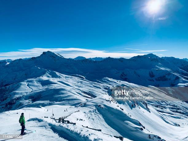 man standing on snowcapped mountain against blue sky - carnet stock photos and pictures