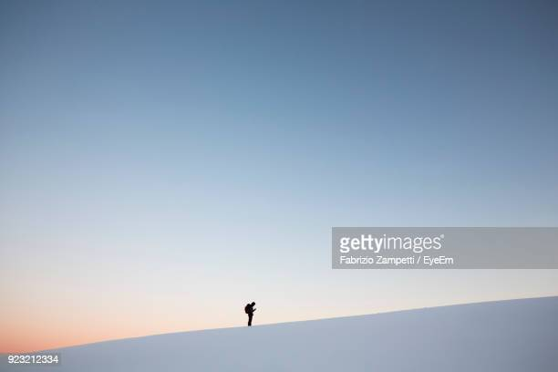 man standing on snowcapped mountain against clear sky at sunset - fabrizio zampetti foto e immagini stock