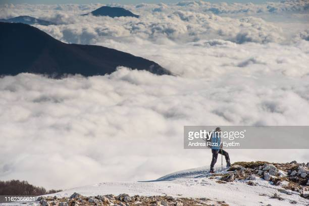 man standing on snowcapped mountain against sky - andrea rizzi foto e immagini stock