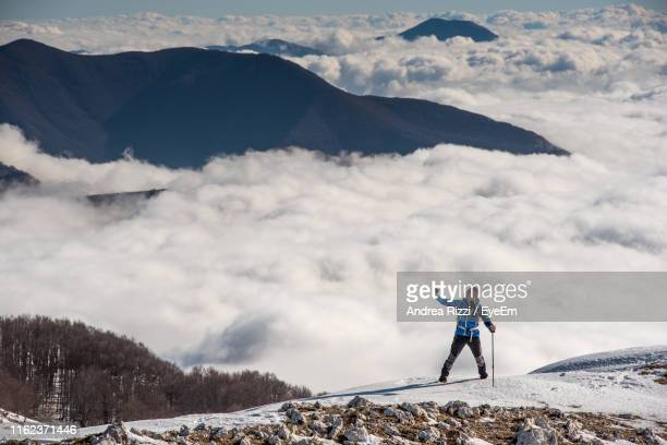 man standing on snowcapped mountain against sky - andrea rizzi stock pictures, royalty-free photos & images