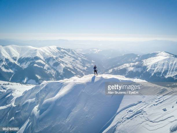 man standing on snowcapped mountain - mountain peak stock pictures, royalty-free photos & images