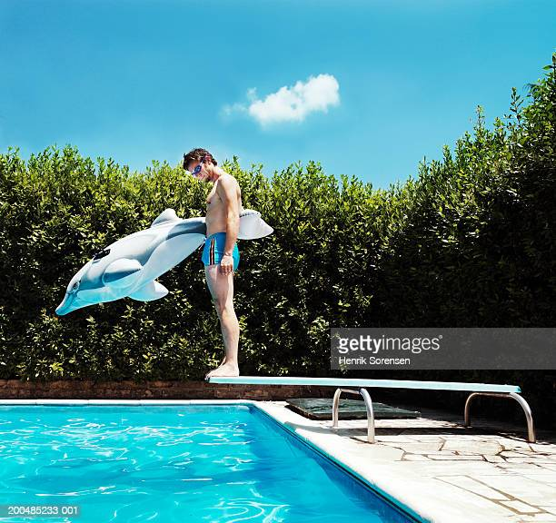 Man standing on springboard beside pool with inflatable toy dolphin