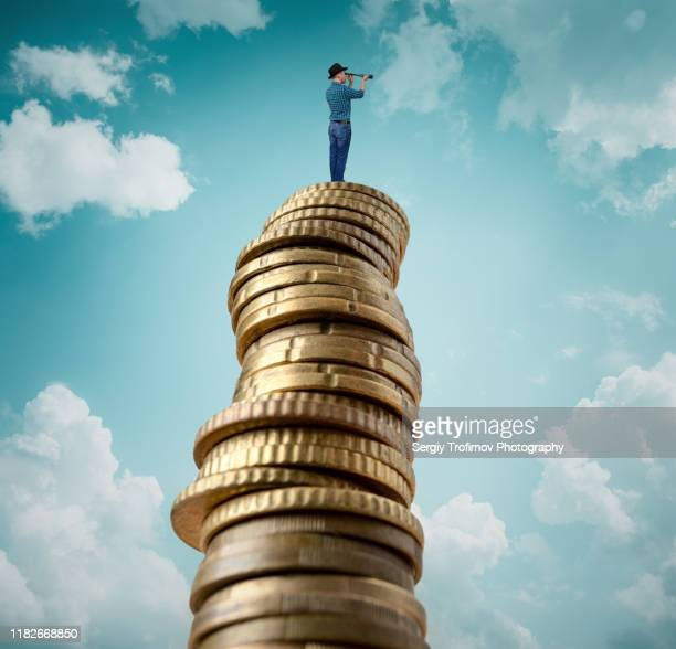 man standing on stack of coins and looking at telescope - wages stock pictures, royalty-free photos & images