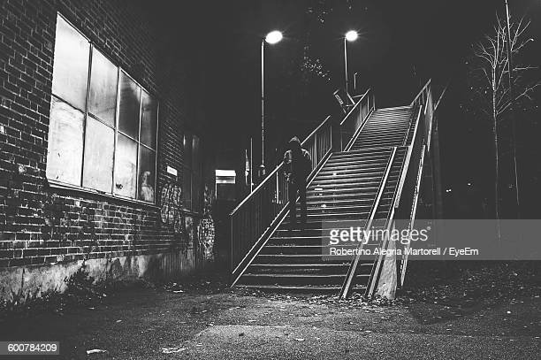 Man Standing On Staircase By Building At Night
