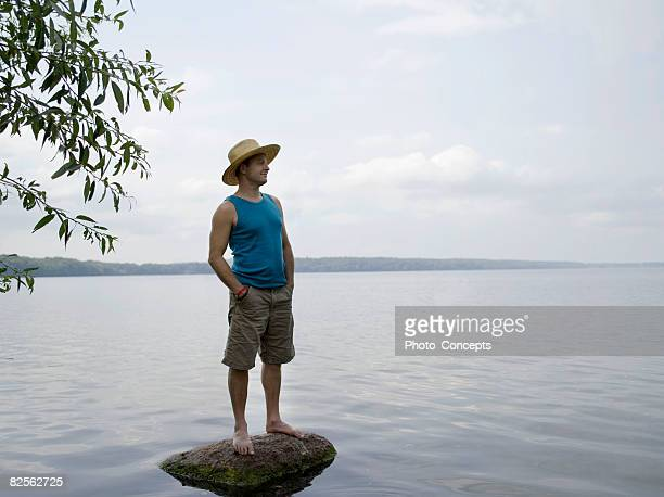 Man standing on stone in shallow water