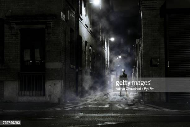 man standing on street at night - alley stock photos and pictures