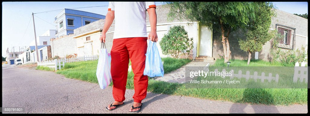 Man Standing On Street Holding Two Plastic Bags : Foto stock