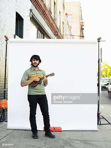 Man standing on street playing ukulele