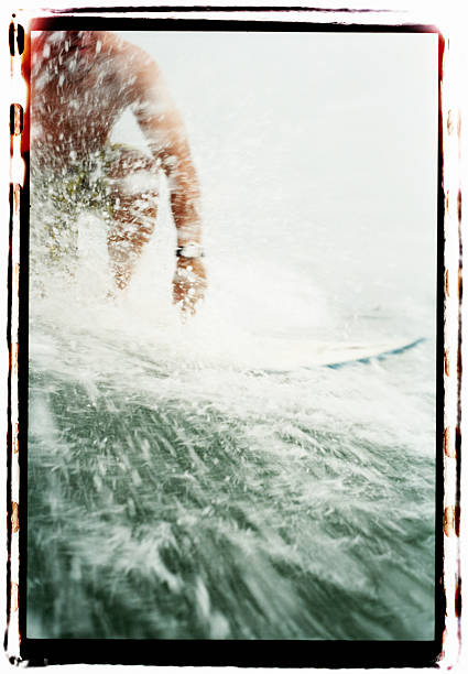 Man standing on surfboard, low angle view