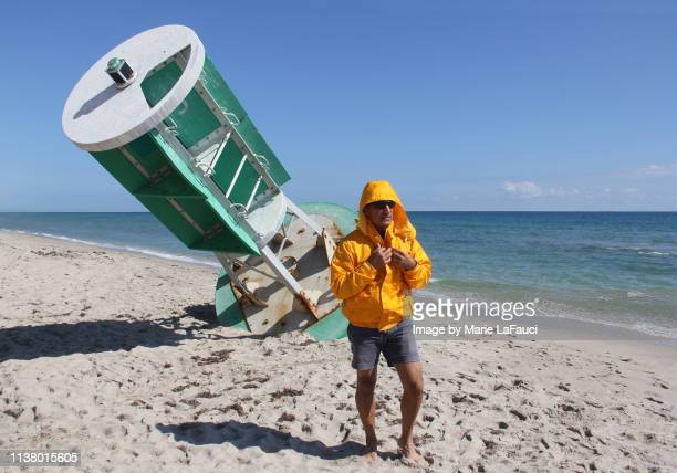 man standing on the beach near a large abandoned channel marker - calm before the storm stock pictures, royalty-free photos & images