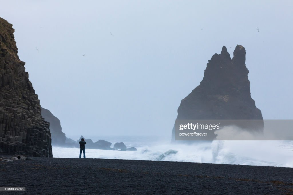 Man Standing on the Beach of the Basalt Cliffs at Reynisdrangar in Iceland : Stock Photo