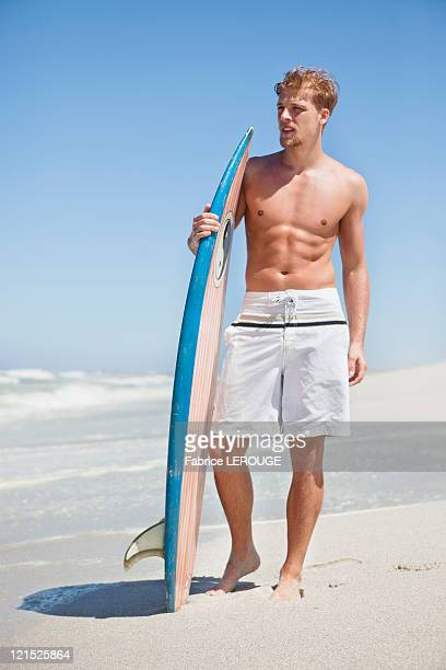 Man standing on the beach with surfboard
