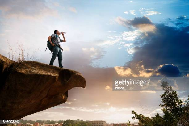 a man standing on the cliff drinking water - só um homem imagens e fotografias de stock