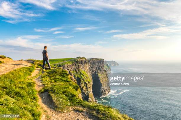 a man standing on the cliffs admires the sunset - rocha imagens e fotografias de stock