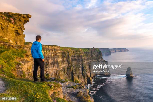 a man standing on the cliffs admires the sunset - republic of ireland stock pictures, royalty-free photos & images