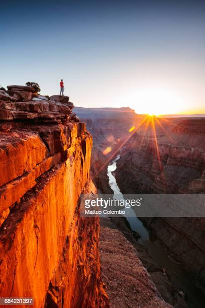 man standing on the edge of grand canyon - canyon foto e immagini stock