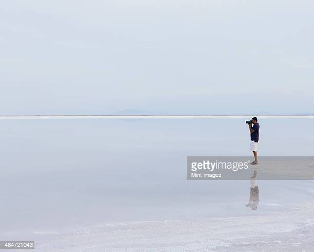 A man standing on the edge of the flooded Bonneville Salt Flats, taking a photograph at dusk.
