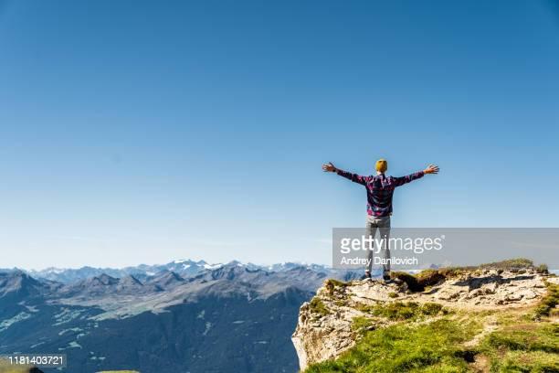 hombre de pie en el borde de la roca con las manos levantadas. alpes italianos cerca de ceceda. - top fotografías e imágenes de stock