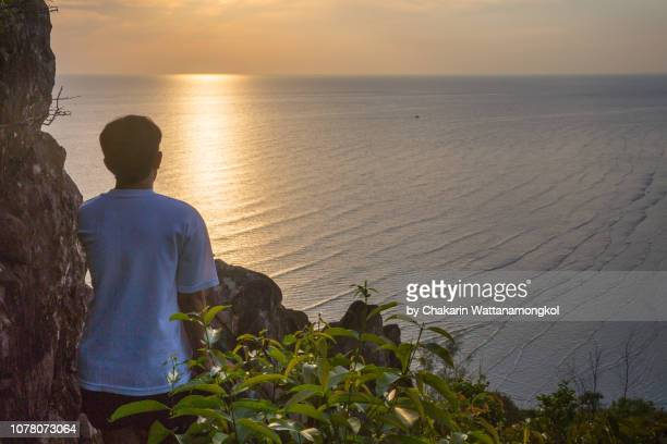 a man standing on the hill top looking at view of chao lao beach at time of sunset, chanthaburi. - chanthaburi sea stock pictures, royalty-free photos & images