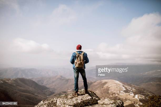 man standing on the mountain top - mountaineering stock pictures, royalty-free photos & images