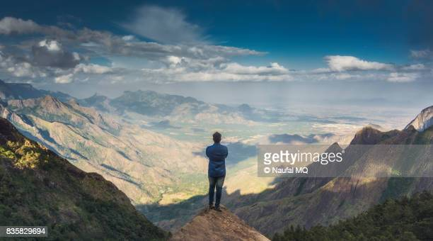 man standing on the peak of the mountain - tranquil scene stock pictures, royalty-free photos & images