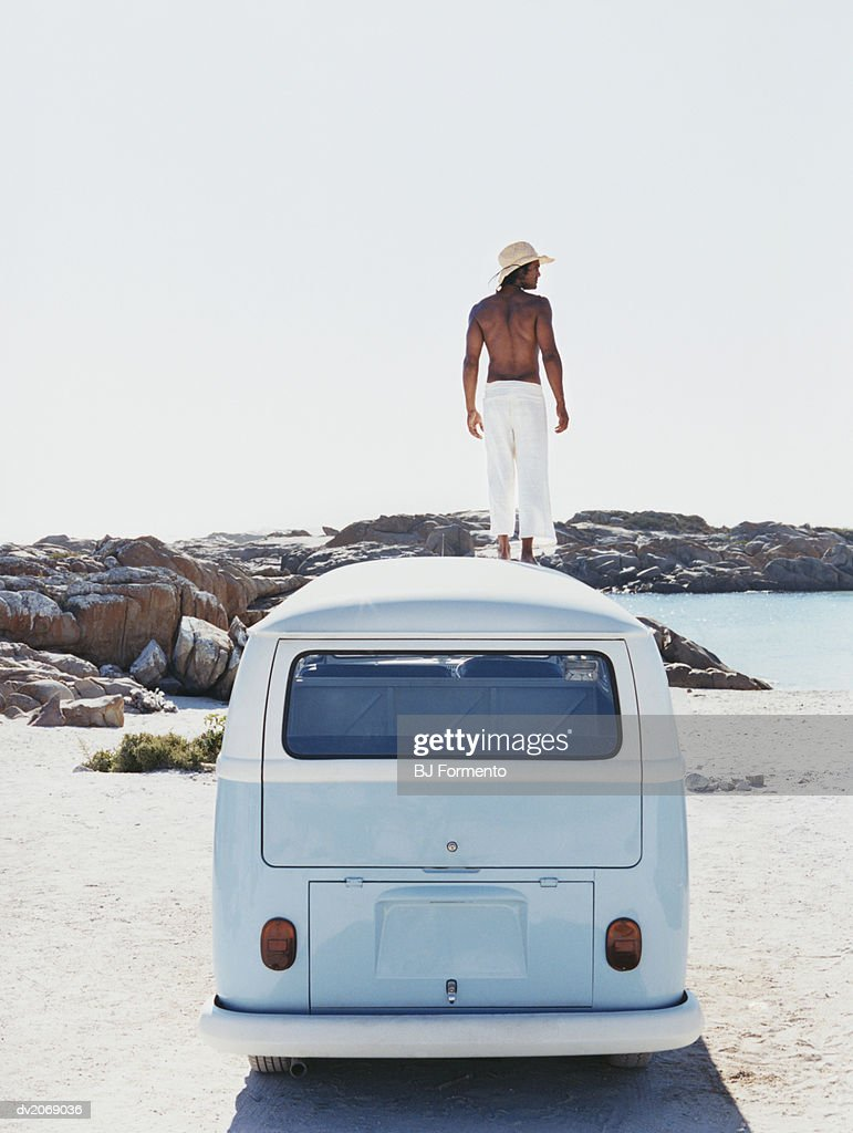 Man Standing on the Roof of a Camping Van Looking at View : Stock Photo