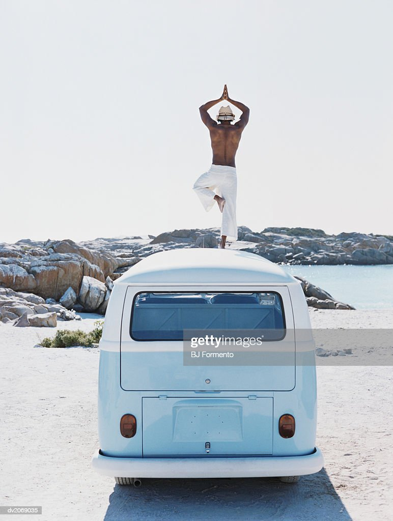 man Standing on the Roof of a Camping Van Practising Yoga : Stock Photo