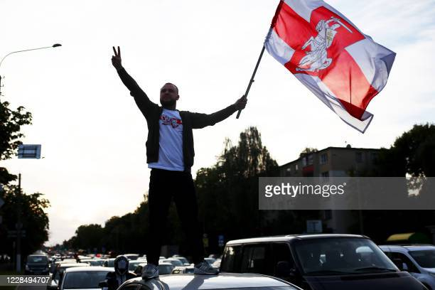 A man standing on the roof of the car waves a former whiteredwhite of Belarus and gestures the Vsign during a rally against the presidential election...