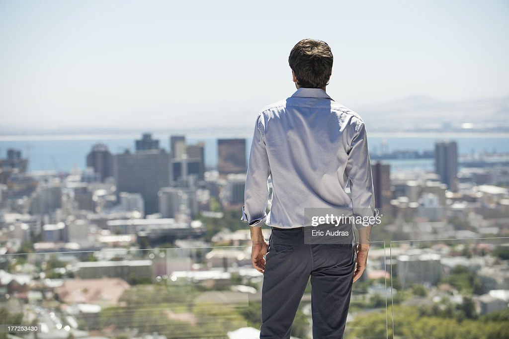 Man standing on the terrace looking at a city : Stock-Foto