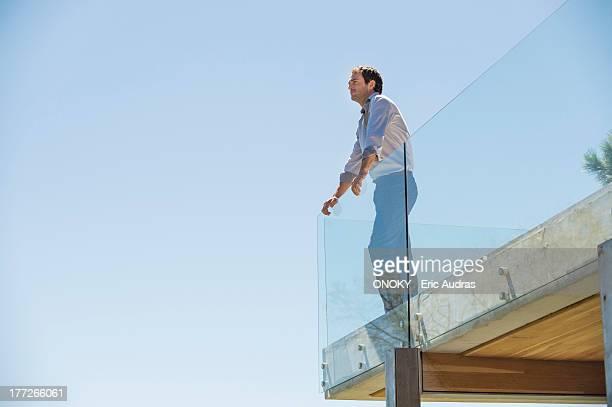 man standing on the terrace looking away - geländer stock-fotos und bilder