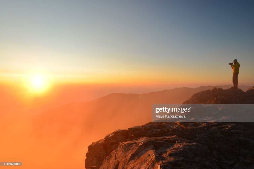 Man standing on top of a mountain at sunrise : Stock Photo
