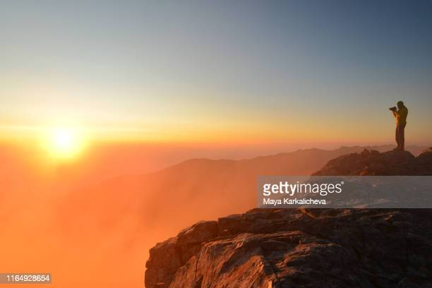 man standing on top of a mountain at sunrise - photographer stock pictures, royalty-free photos & images