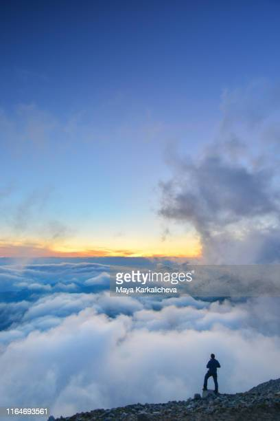 man standing on top of a mountain over the clouds at sunset - libre de droit photos et images de collection