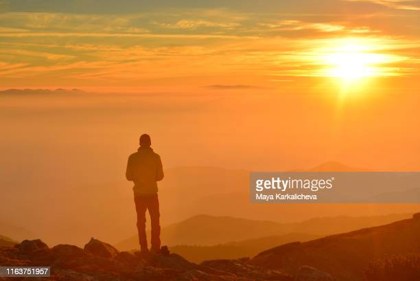 man standing on top of a mountain watching the sunset - pirin mountains stock pictures, royalty-free photos & images