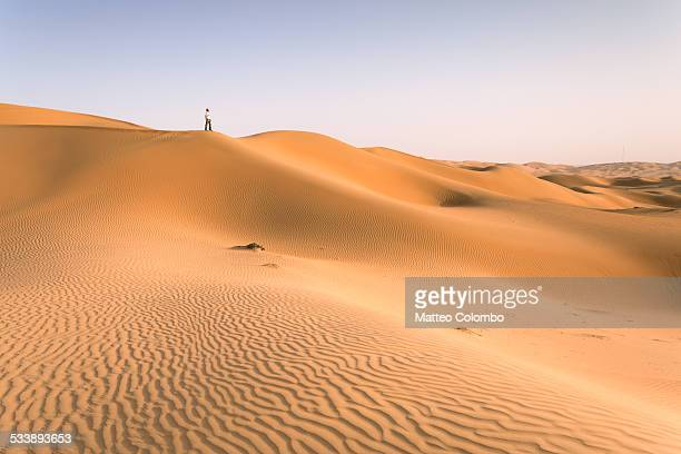 man standing on top of desert sand dune at dawn - sand dune stock pictures, royalty-free photos & images