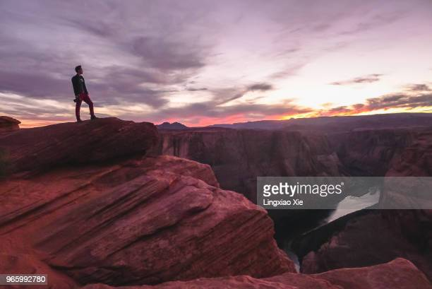 man standing on top of horseshoe bend overlooking colorado river, arizona, usa - cresta de montanha - fotografias e filmes do acervo
