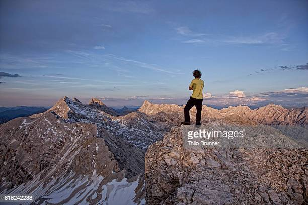 Man standing on top of mountain and looking at view