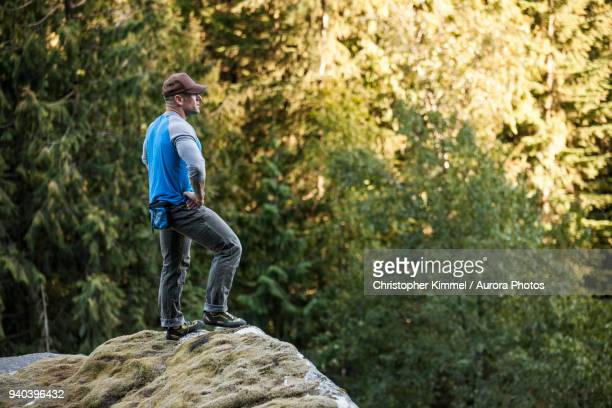 man standing on top of rock with arms akimbo while bouldering near elbow lake in fraser valley, harrison mills, british columbia, canada - arms akimbo stock pictures, royalty-free photos & images