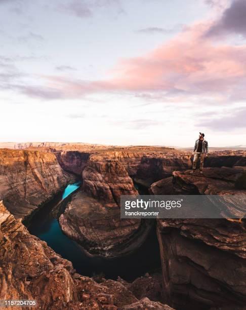 mann steht auf der hufeisenkurve in usa - canyon stock-fotos und bilder